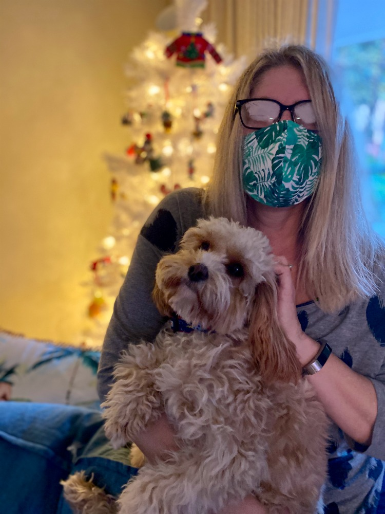 woman wearing a face mask holding a dog in front of a christmas tree