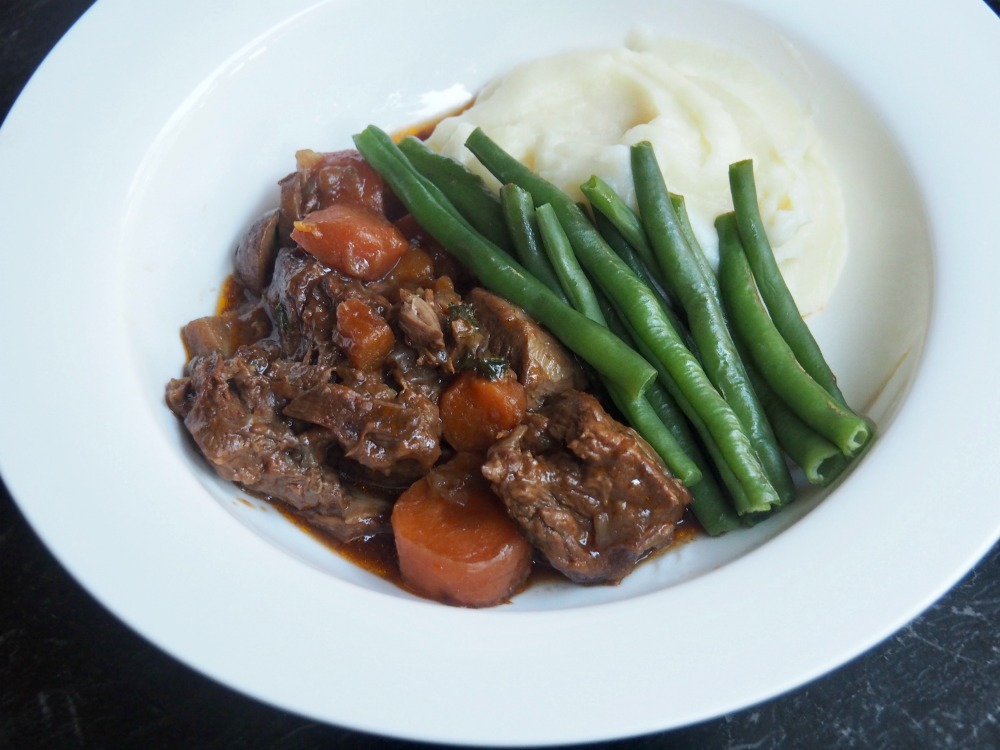 beef and ale stew with mash and green beans on a plate