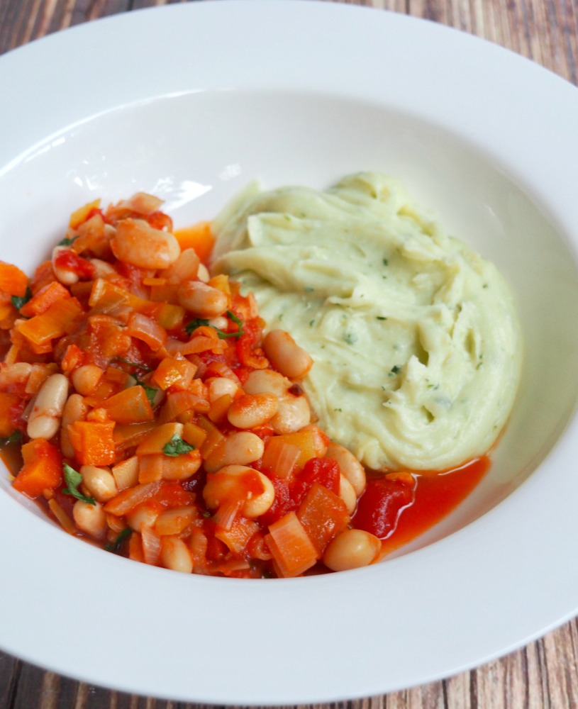 cider bean stew with cheddar and parley mash on a plate