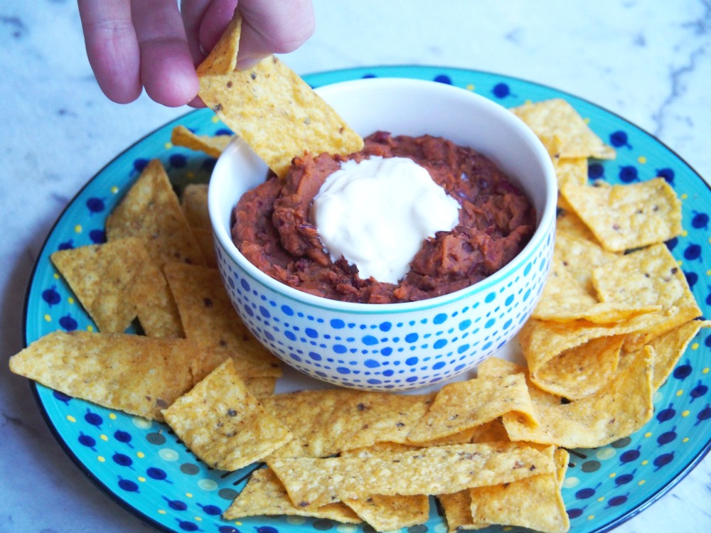 tortilla chip dipped in Mexican bean dip