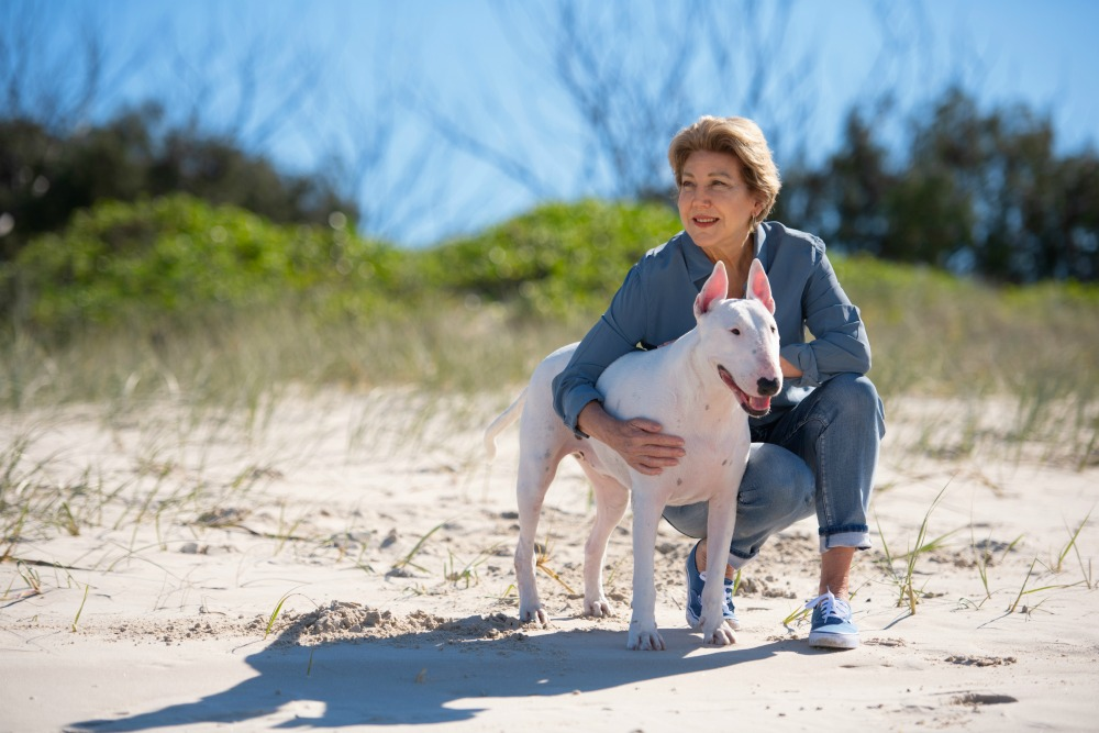woman hugging her dog on the beach