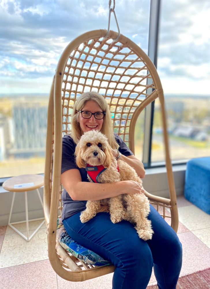 woman holding cavoodle in swinging chair