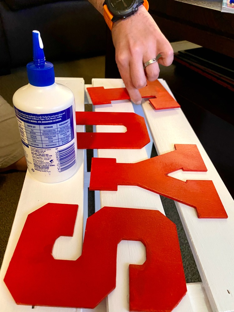 sticking letters on to wooden toy box