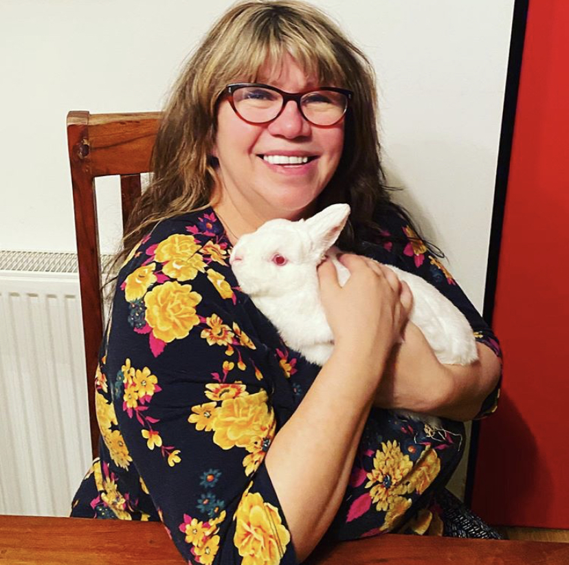 woman wearing glasses and holding a white rabbit