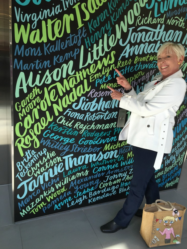 Carole Matthews author pointing at her name on a wall