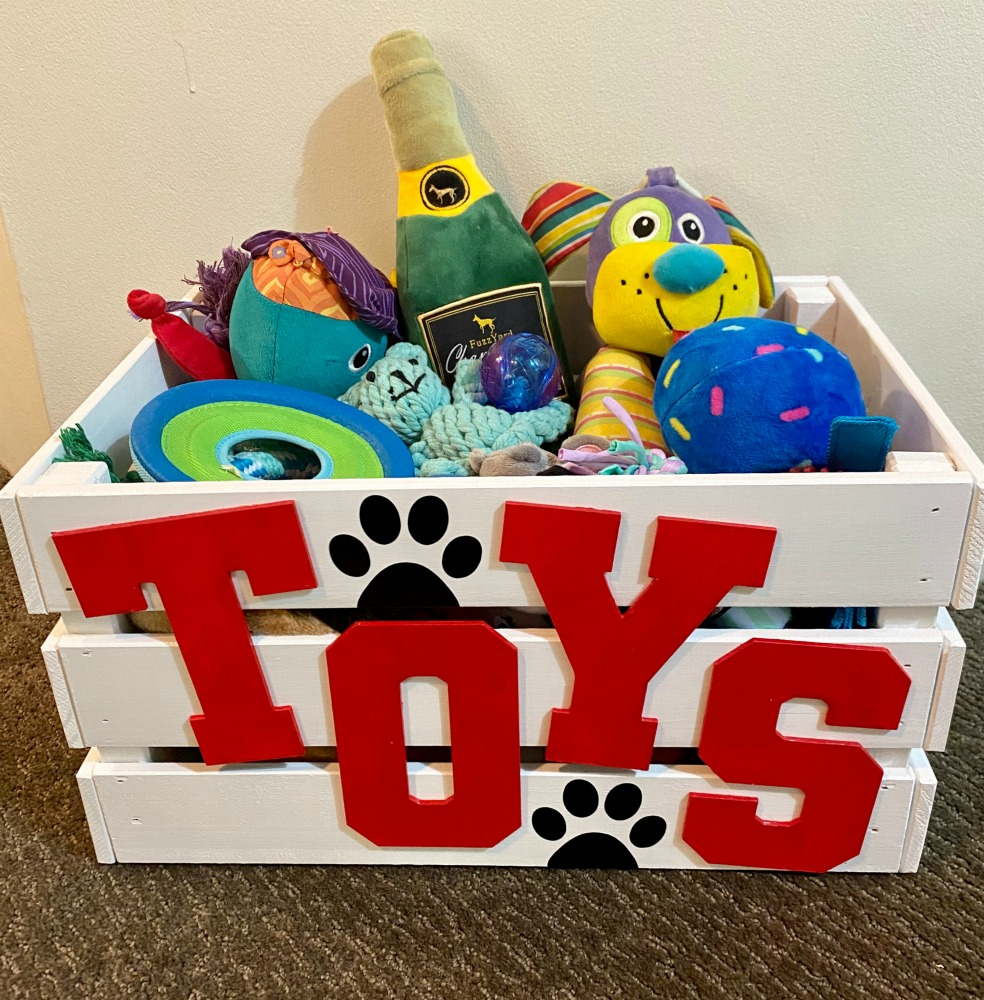 white toy box with red writing spelling toys