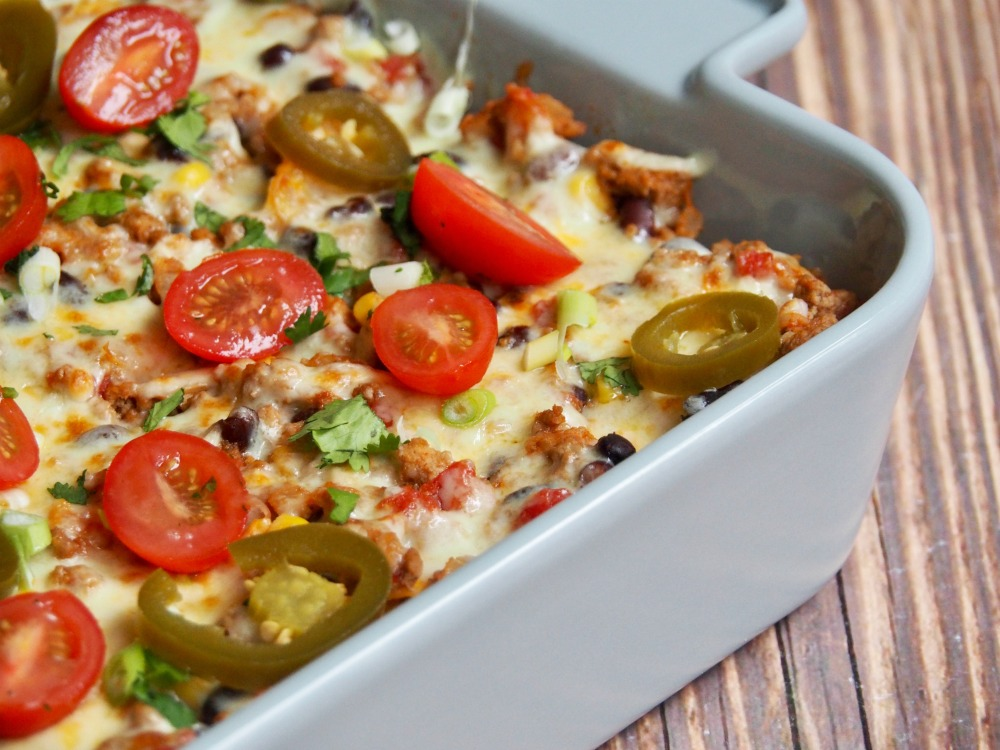 loaded turkey nachos topped with cheese coriander and cherry tomatoes