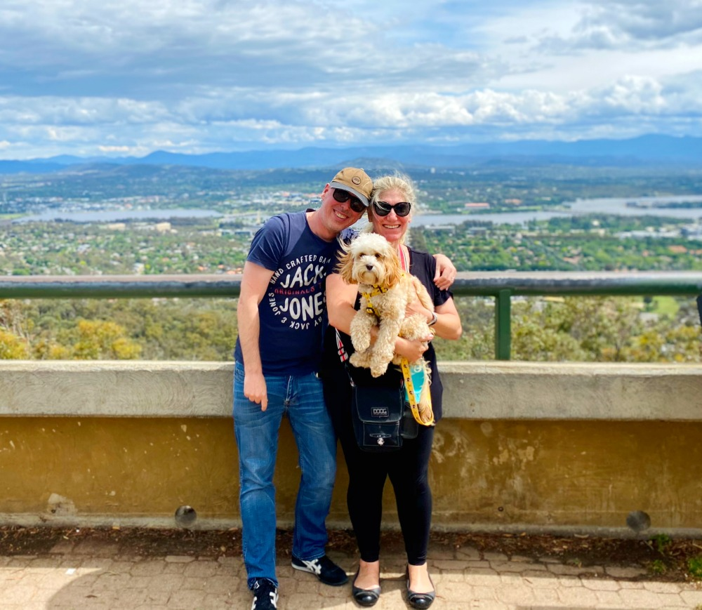a couple holding a cavoodle at the top of mount ainslie