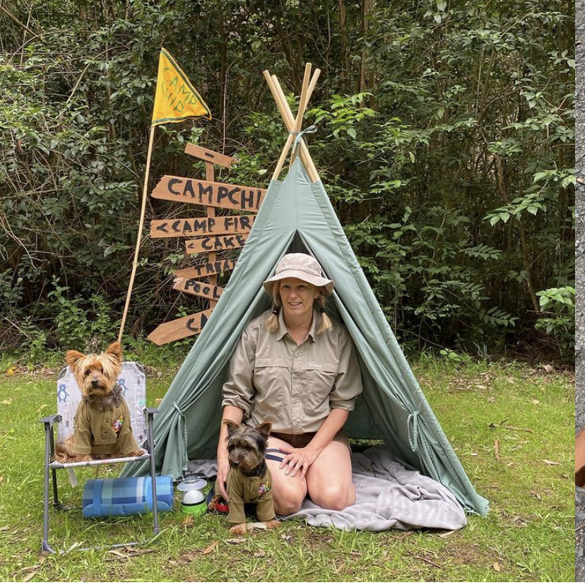 a woman in scout uniform sitting in a teepee with her dog
