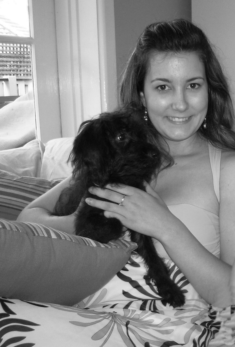 black and white picture of woman cuddling black dog