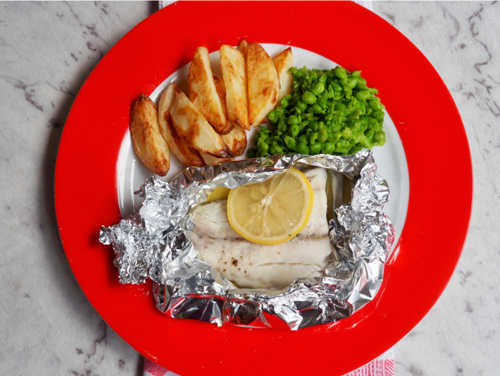 oven baked fish fillets with smashed peas and handcut chips on plate