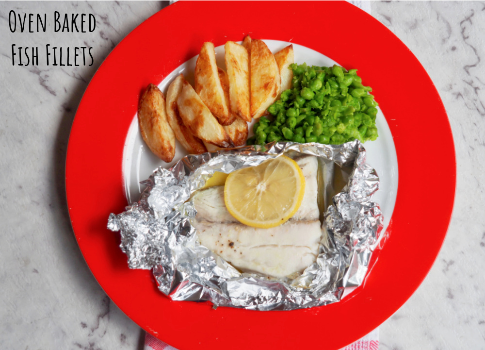 oven baked fish fillets with a slice of lemon on top handcut chips and smashed peas
