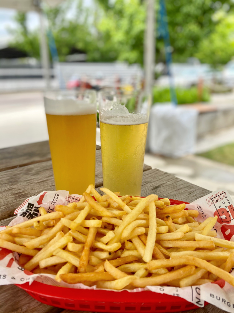 two glasses of beer and basket of fries