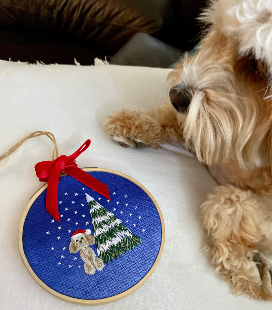 embroidered hoop of a cavoodle sitting next to a christmas tree