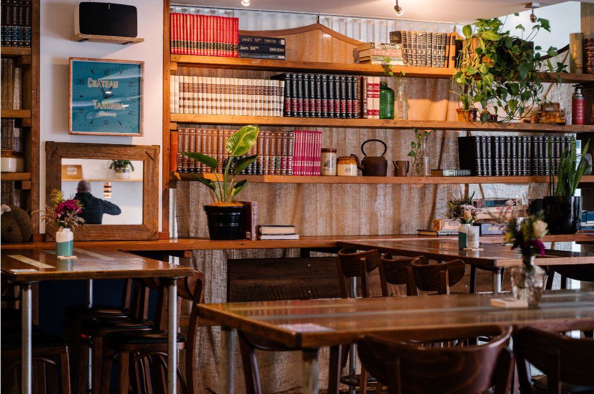 Book lined shelves and wooden tables in cosy bar