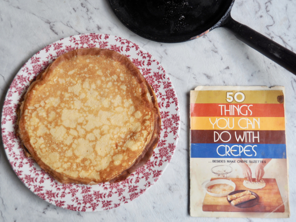 crepe pan recipe book and stack of crepes