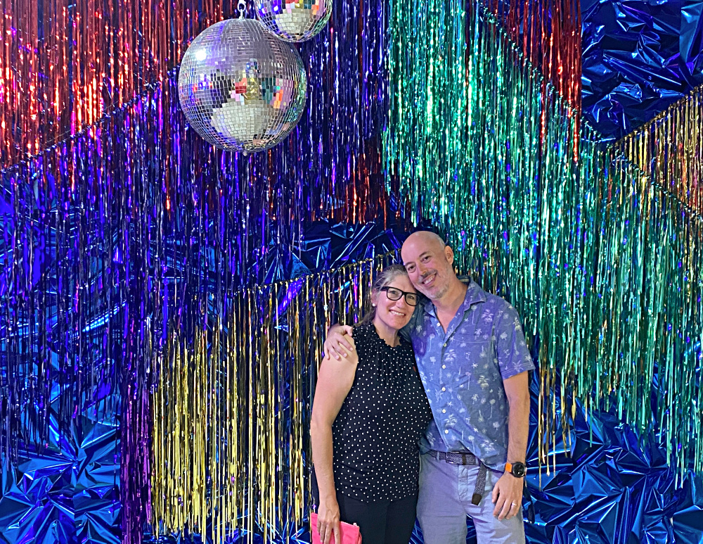 couple standing in front of a glittery background