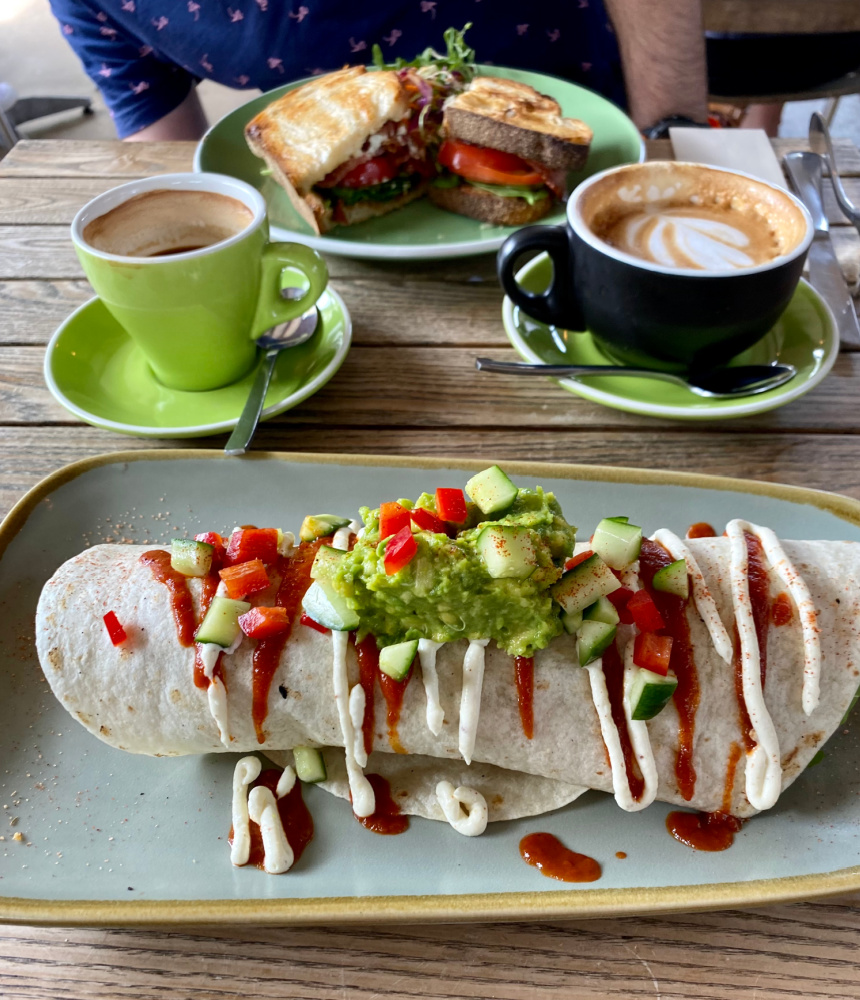 burrito topped with guac and coffee cup in background