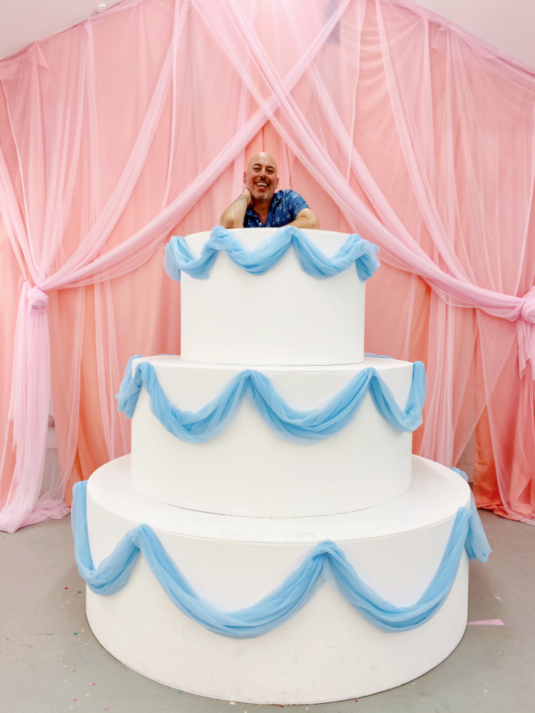 man looking out of life size wedding cake