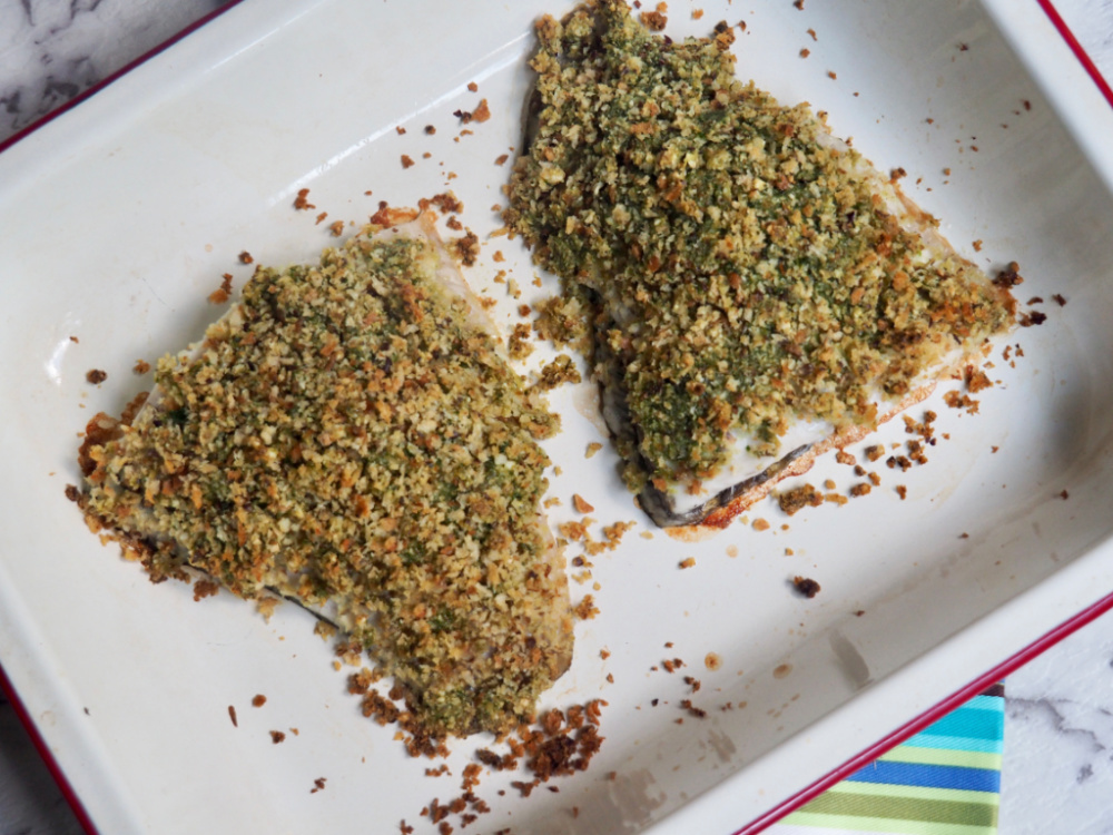 two fillets of pesto crumbed fish in baking dish