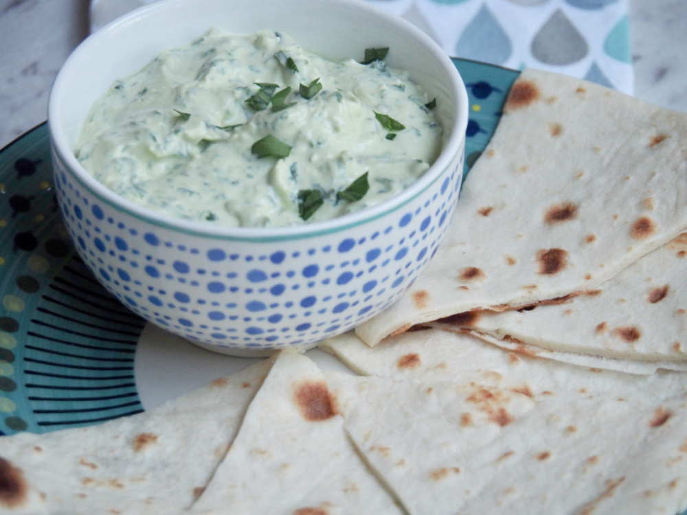 spinach and feta dip in bowl on plate surrounded by flatbread