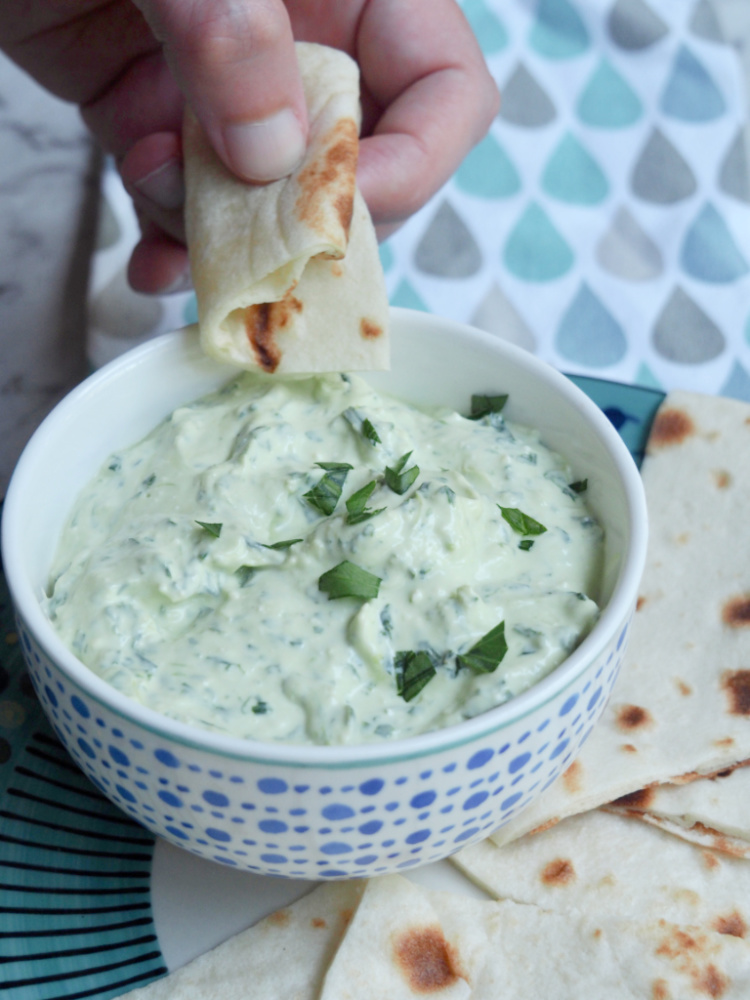 dipping bread into bowl of spinach and feta dip