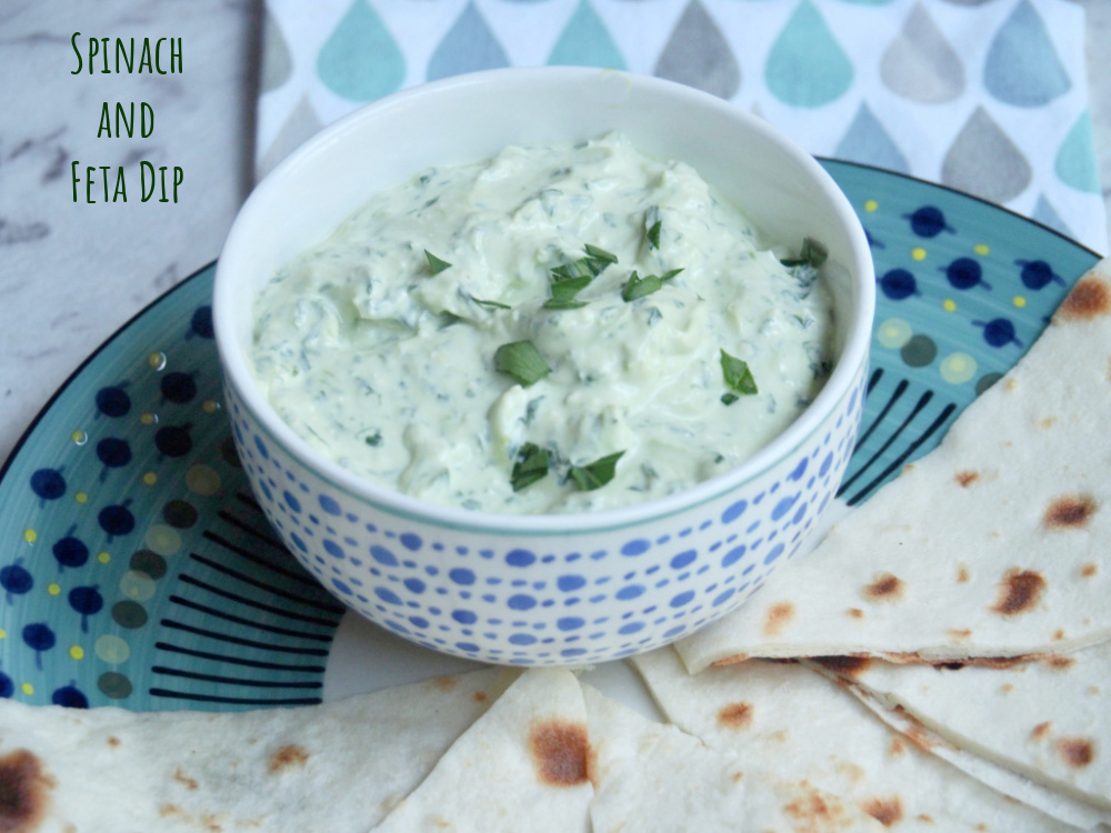spinach and feta dip in small bowl on plate with flatbread