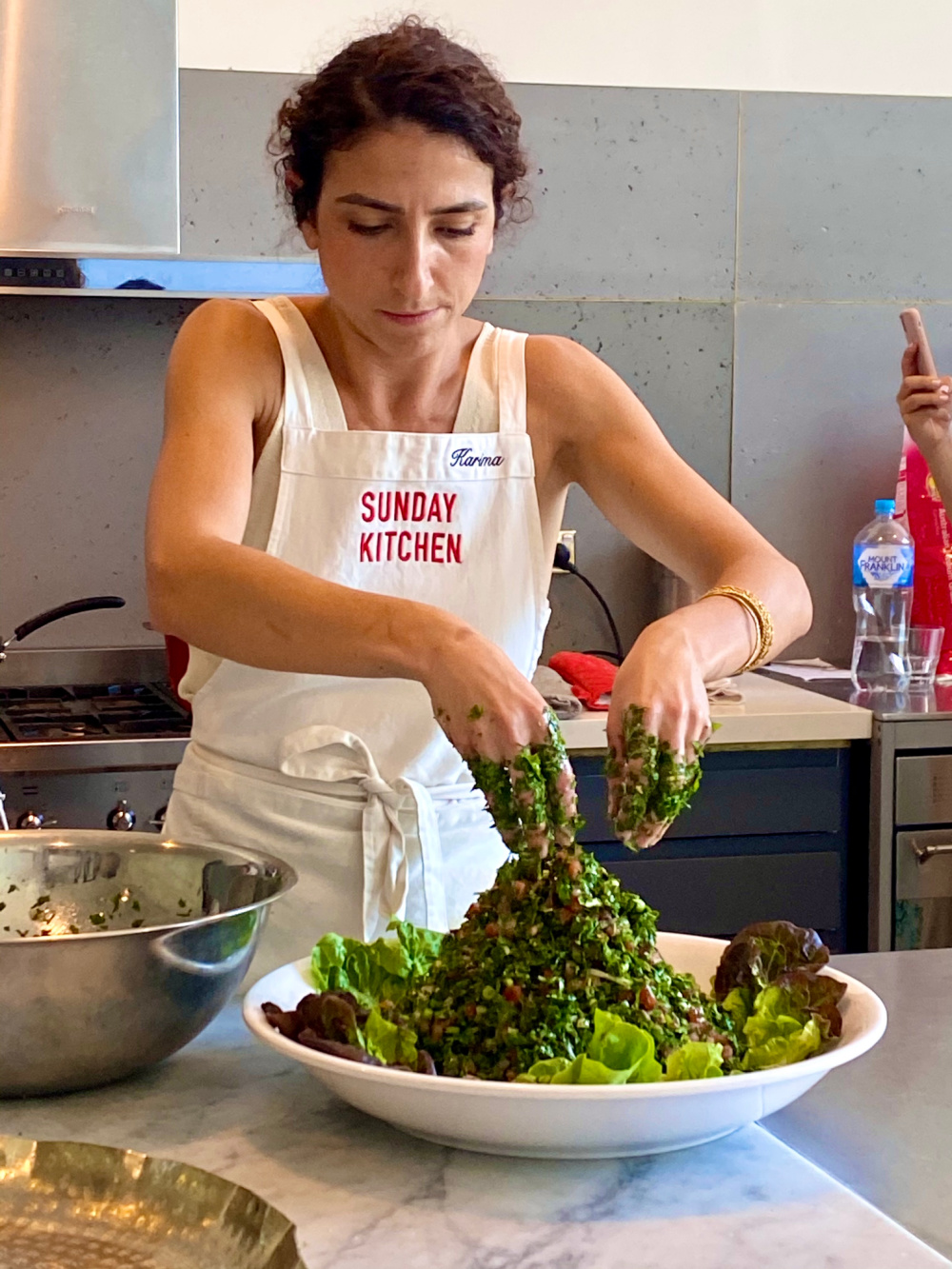 woman using hands to mix a giant bowl of tabbouleh