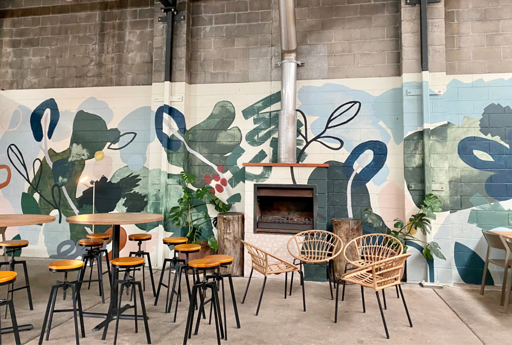 high chairs and table in industrial looking cafe with wall mural