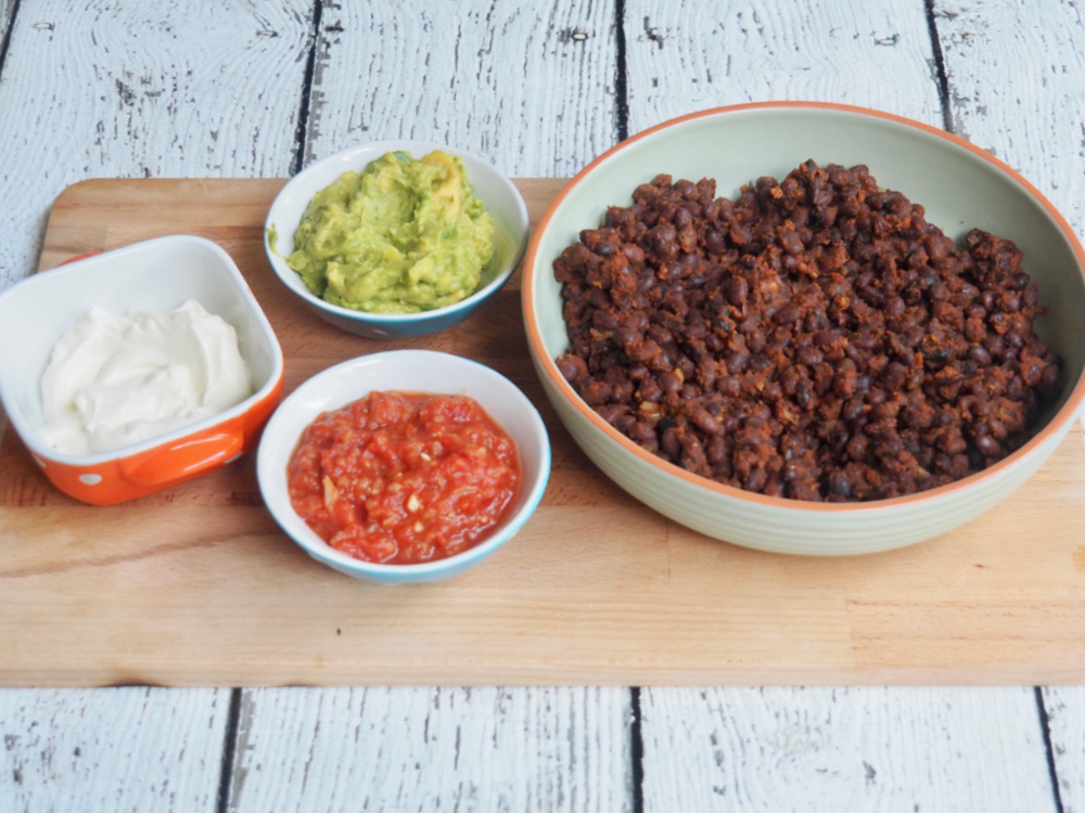 black bean chilli on board with small bowls of sour cream salsa and guacamole