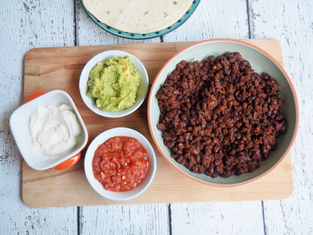 bowl of black bean chilli with small bowls of guacamole and salsa