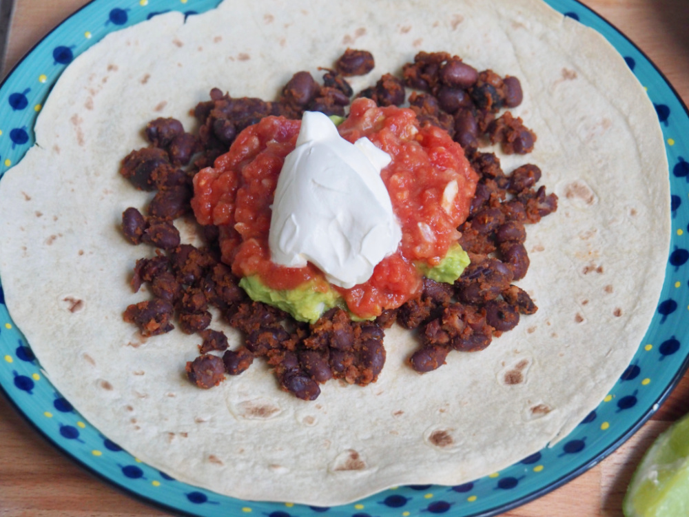 tortilla loaded with black beans sour cream guacamole and sour cream