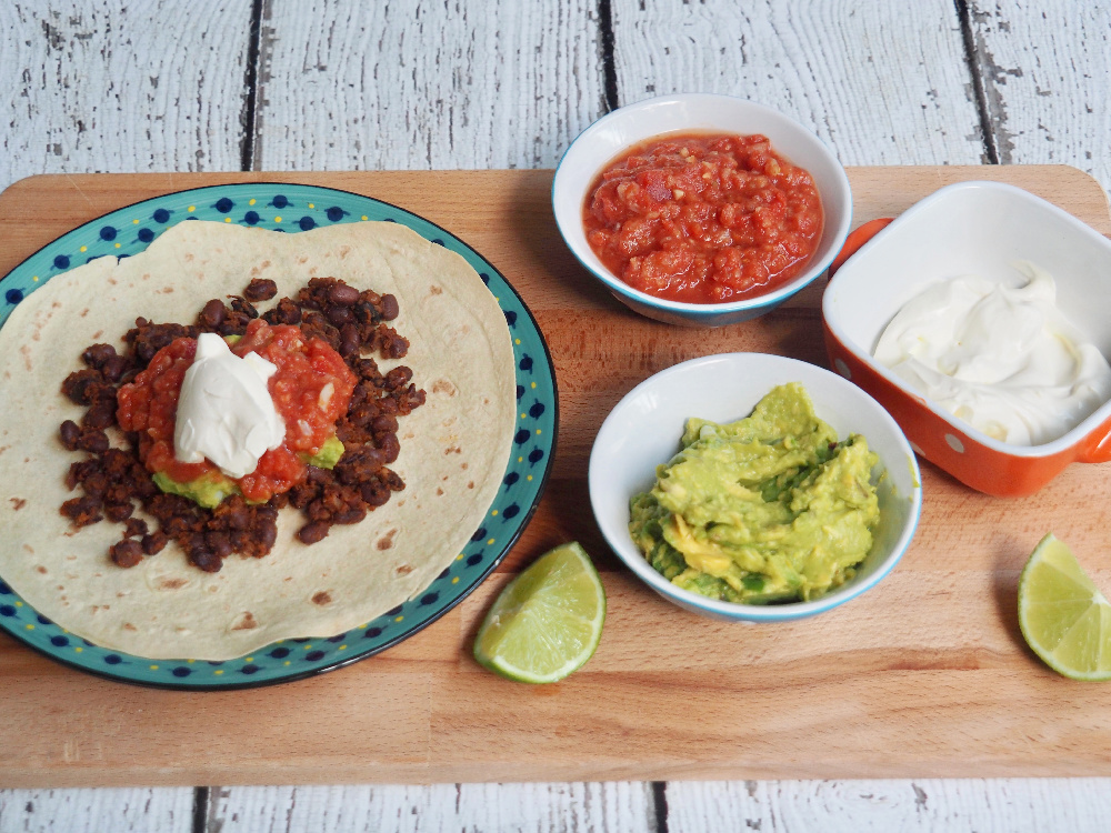 black bean chilli on tortilla with salsa guacamole and sour cream