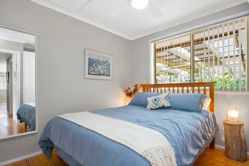 queen size bed with blue bed linen and wooden headboard