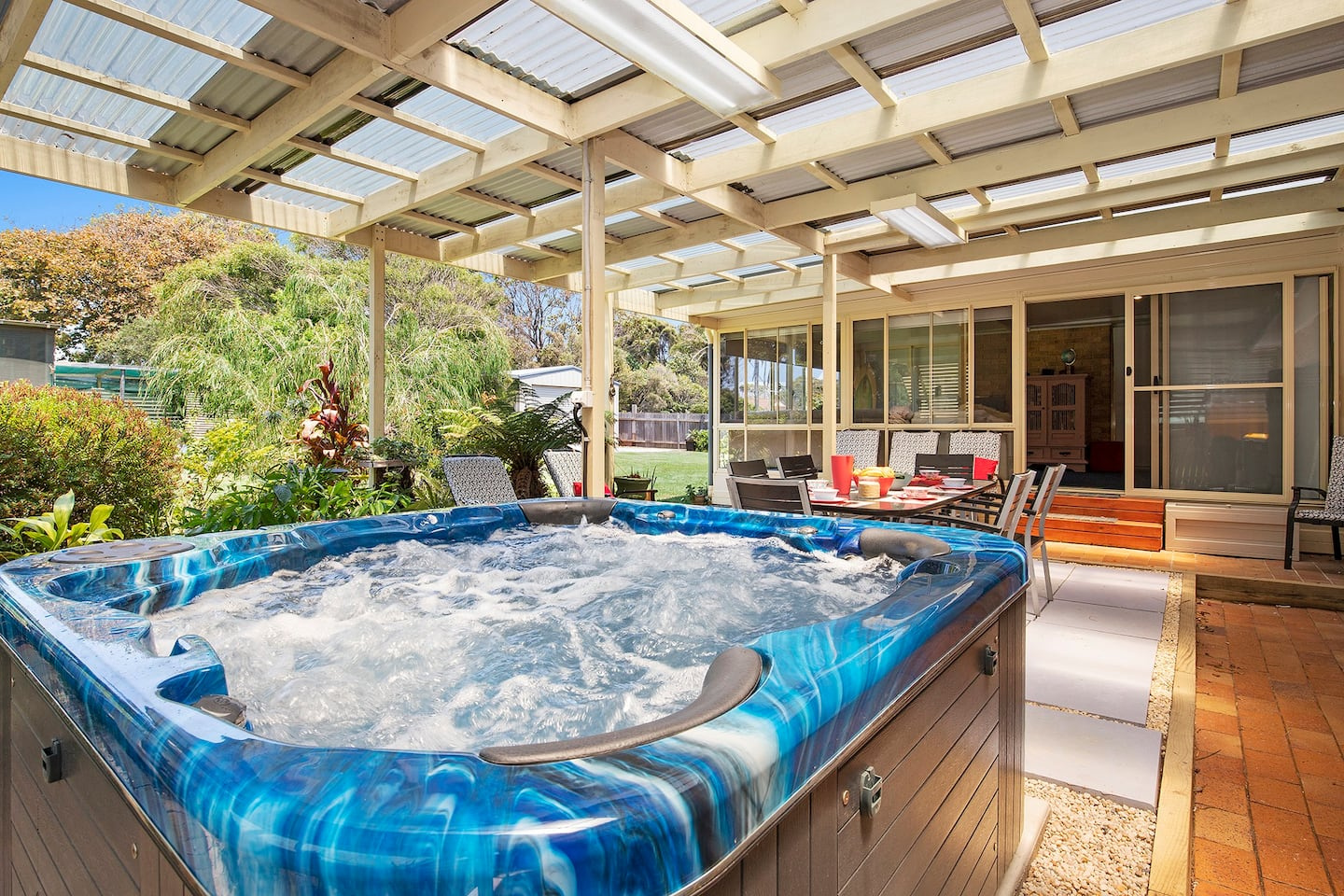 jacuzzi looking out on to covered outside entertainment area and lush garden to side