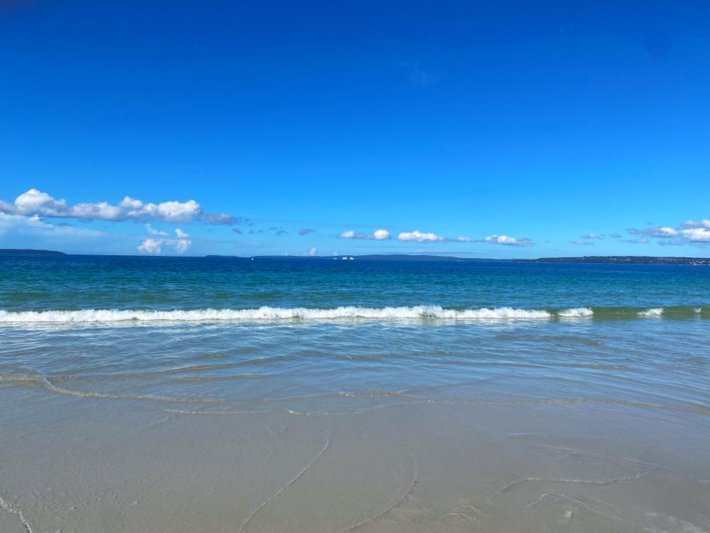 deep blue sky and waves crashing on to sand
