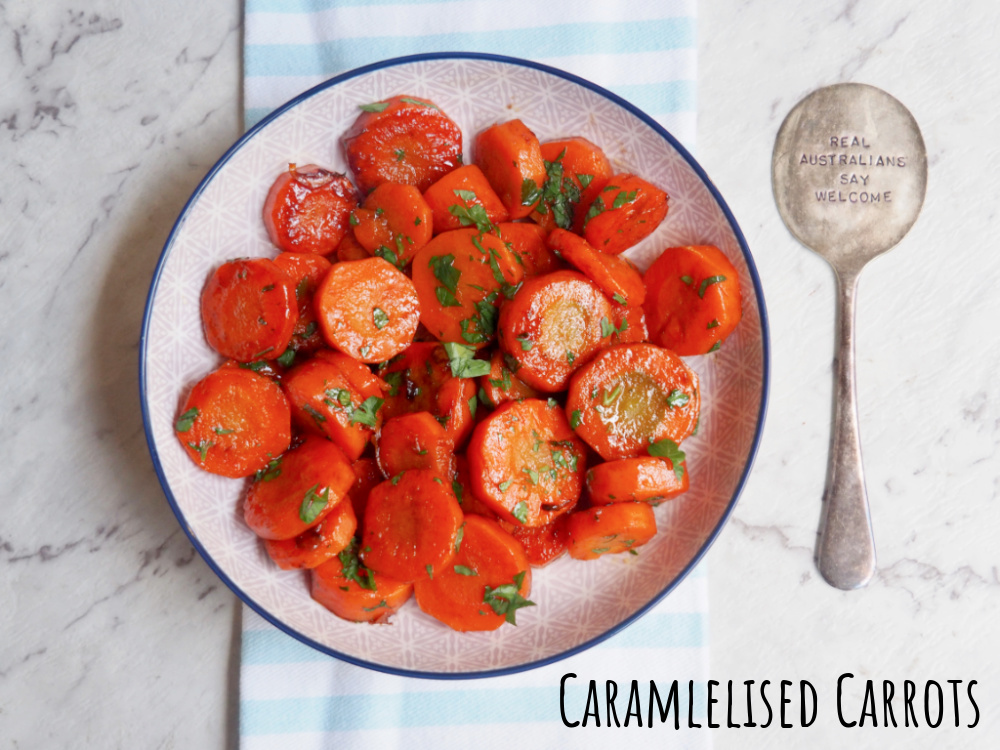 bowl of caramelised carrots next to a spoon that says real Australians say welcome