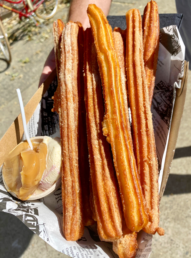 churros with caramel sauce and ice cream beach is in the background