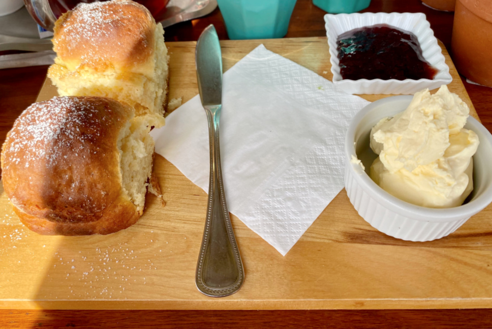 two scones on board with pot of cream and pot of jam