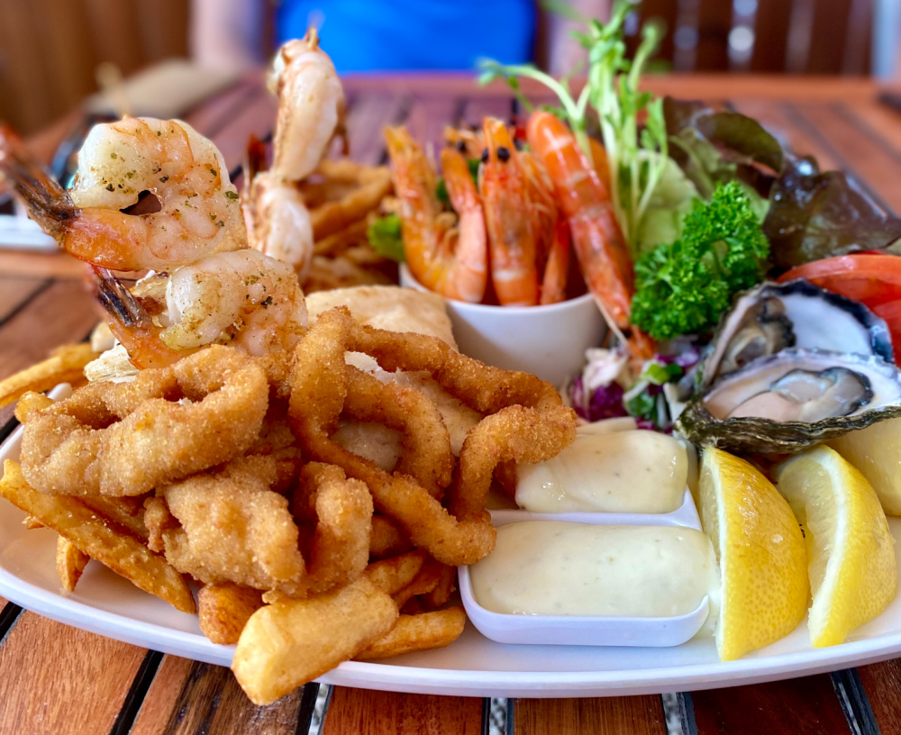 seafood basket with grilled fish prawns oysters and beer battered chips