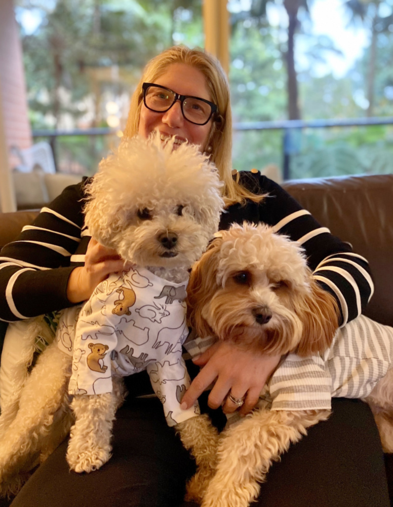 woman cuddling two oodle dogs
