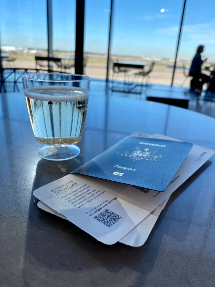 a passport boarding pass and glass of prosecco