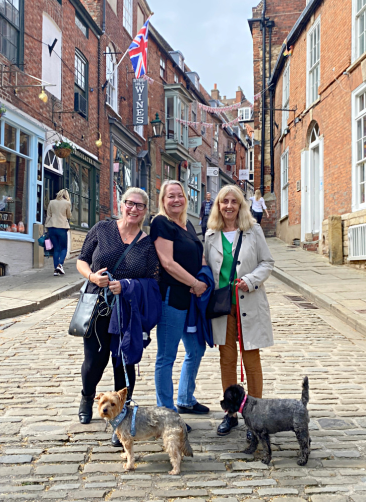 three women standing with 2 dogs at the bottom of an old fashioned steep hill