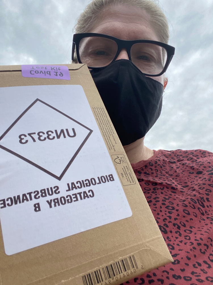 woman wearing a black face mask with a box of home covid test