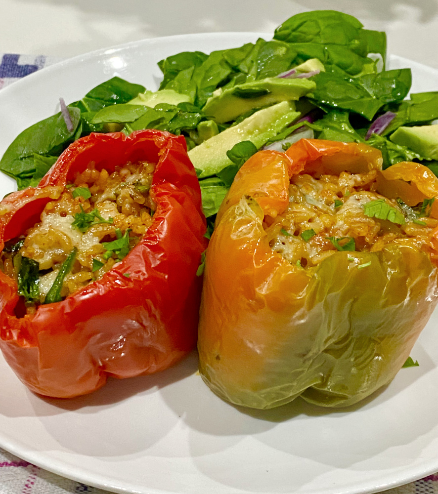 two pesto stuffed peppers on a plate
