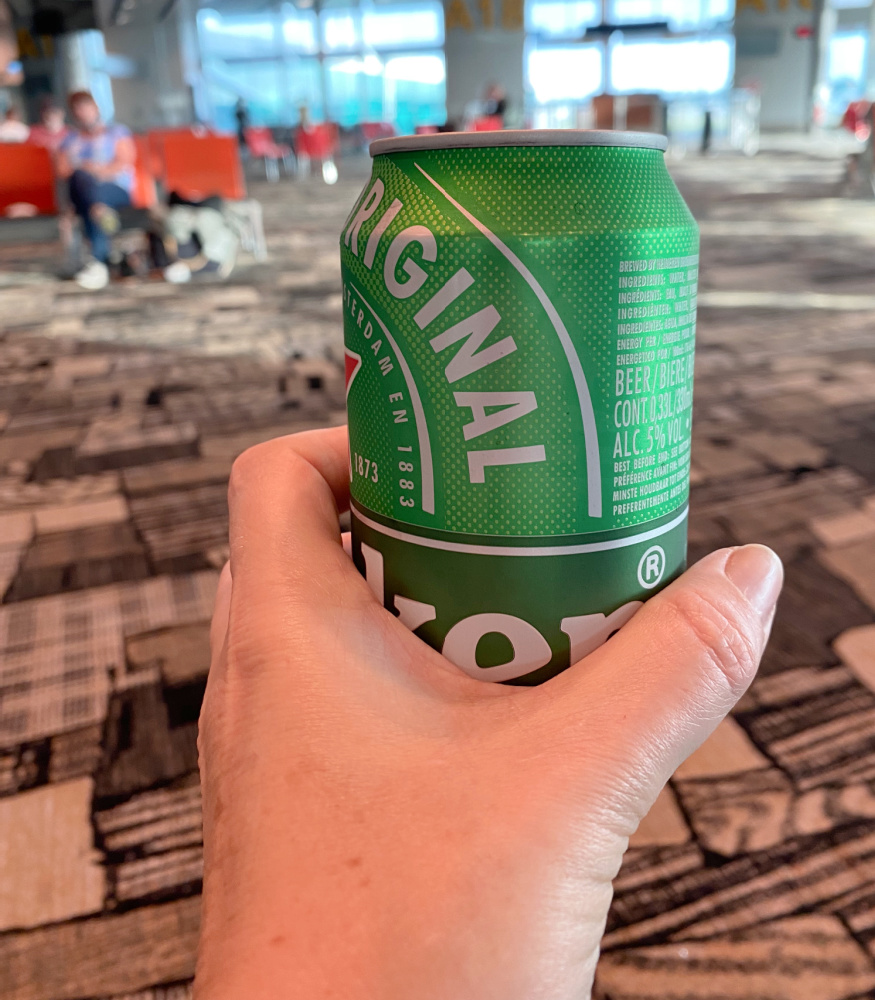 hand holding a can of beer at airport gate