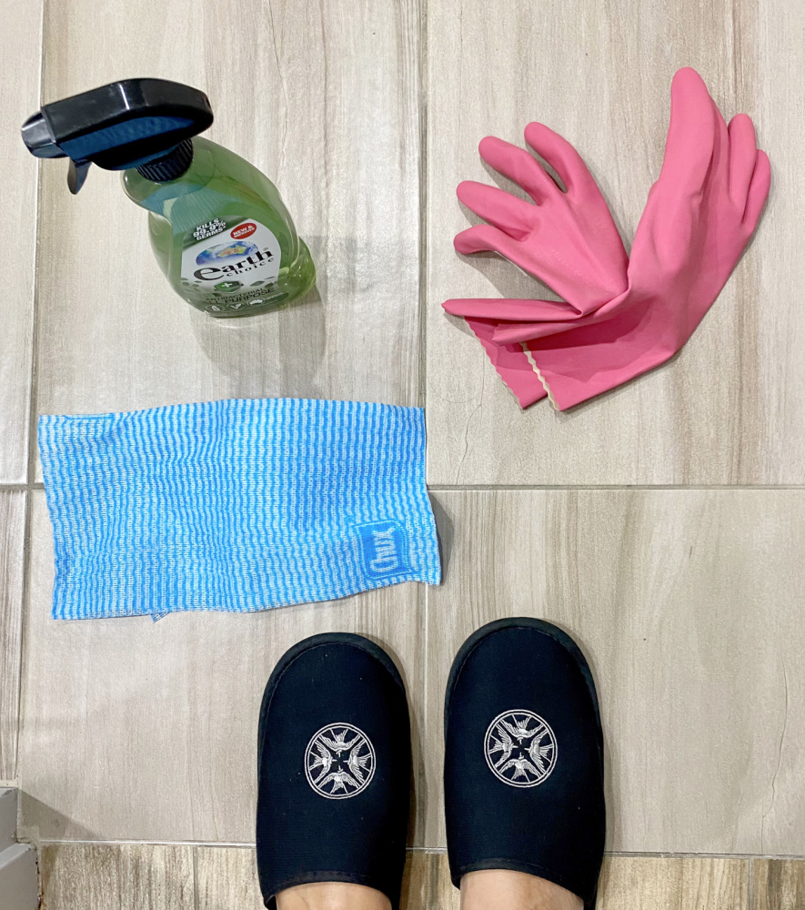 a bottle of cleaning fluid, rubber gloves and j cloth