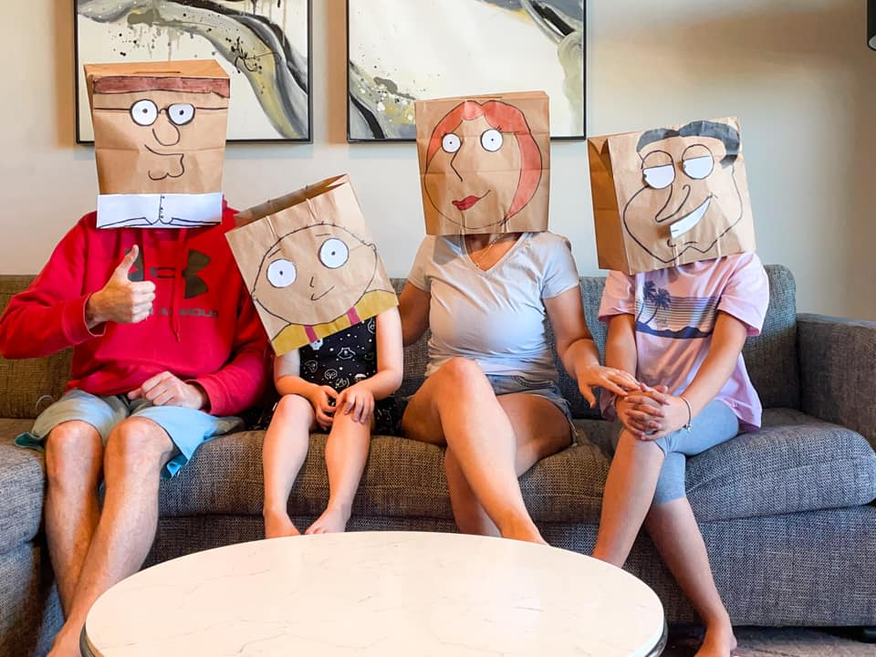 family of four sitting on sofa wearing paper bags decorated with funny faces over their heads