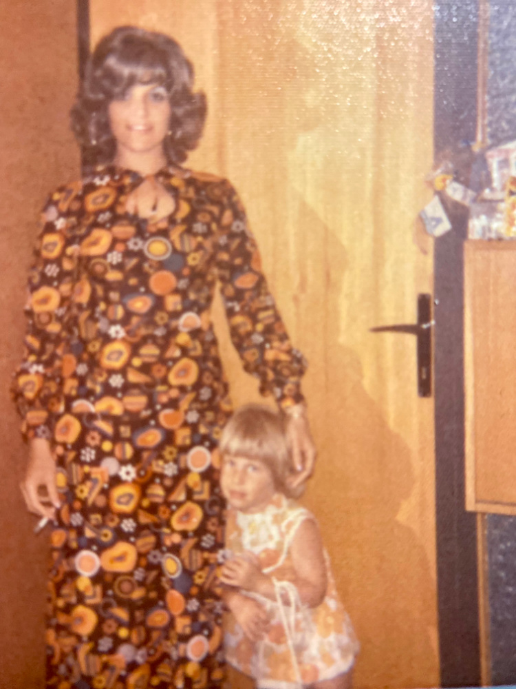 woman in 70s maxi dress with small child next to her