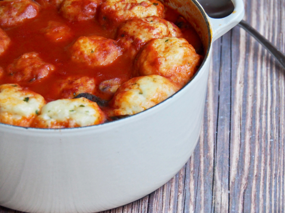 side view of pot of paprika chicken stew with chive dumplings